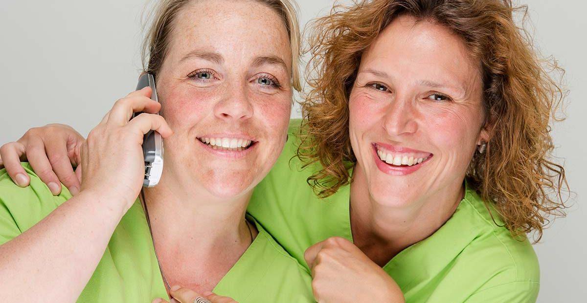 Mitarbeiterin Bernadette Mendel und Mitarbeiterin Cornelia Renneberg lächeln in die Kamera, während Bernadette Mendel den Telefonhörer ans Ohr hält.