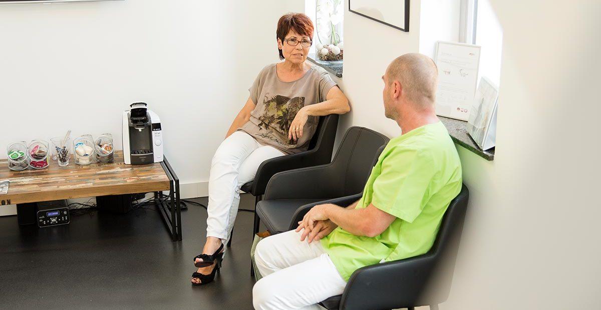 Dr. Buchmann spricht mit einer älteren Patientin im Wartezimmer.