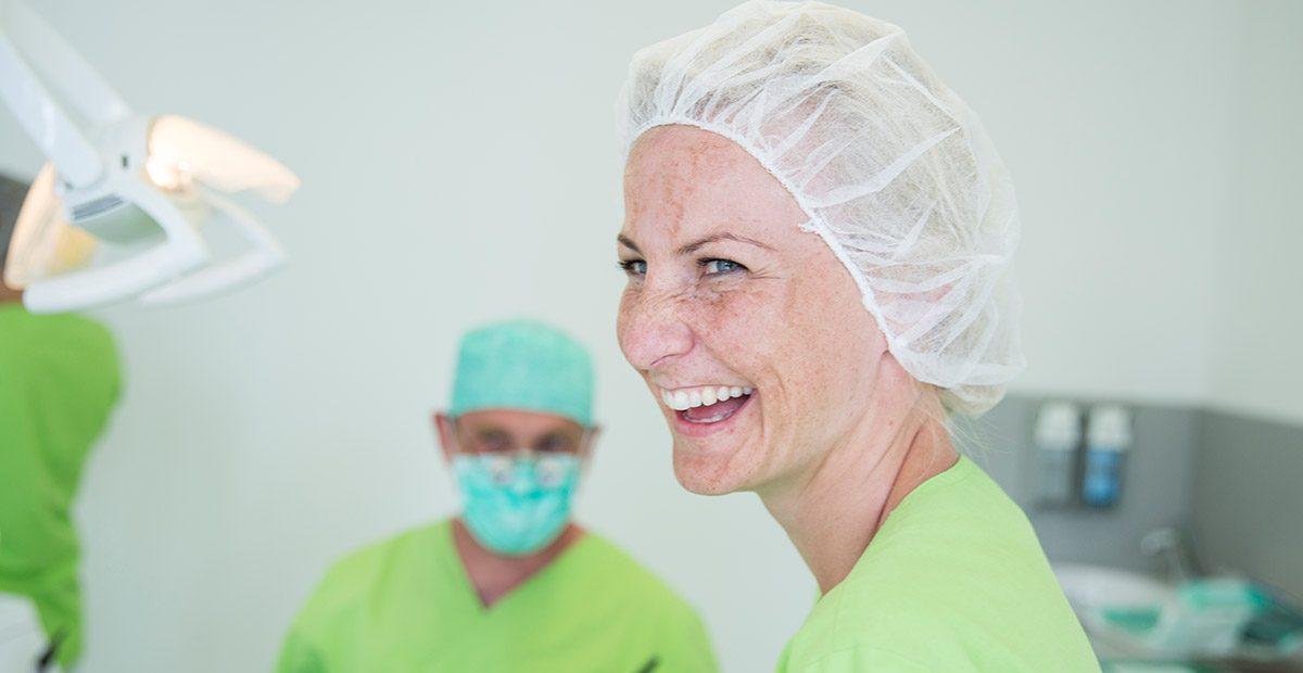 Mitarbeiterin Franziska Büchler lacht im OP-Raum mit Haube auf dem Kopf. Im Hintergrund ist Dr. Buchmann zu sehen, auch mit Haube auf dem Kopf