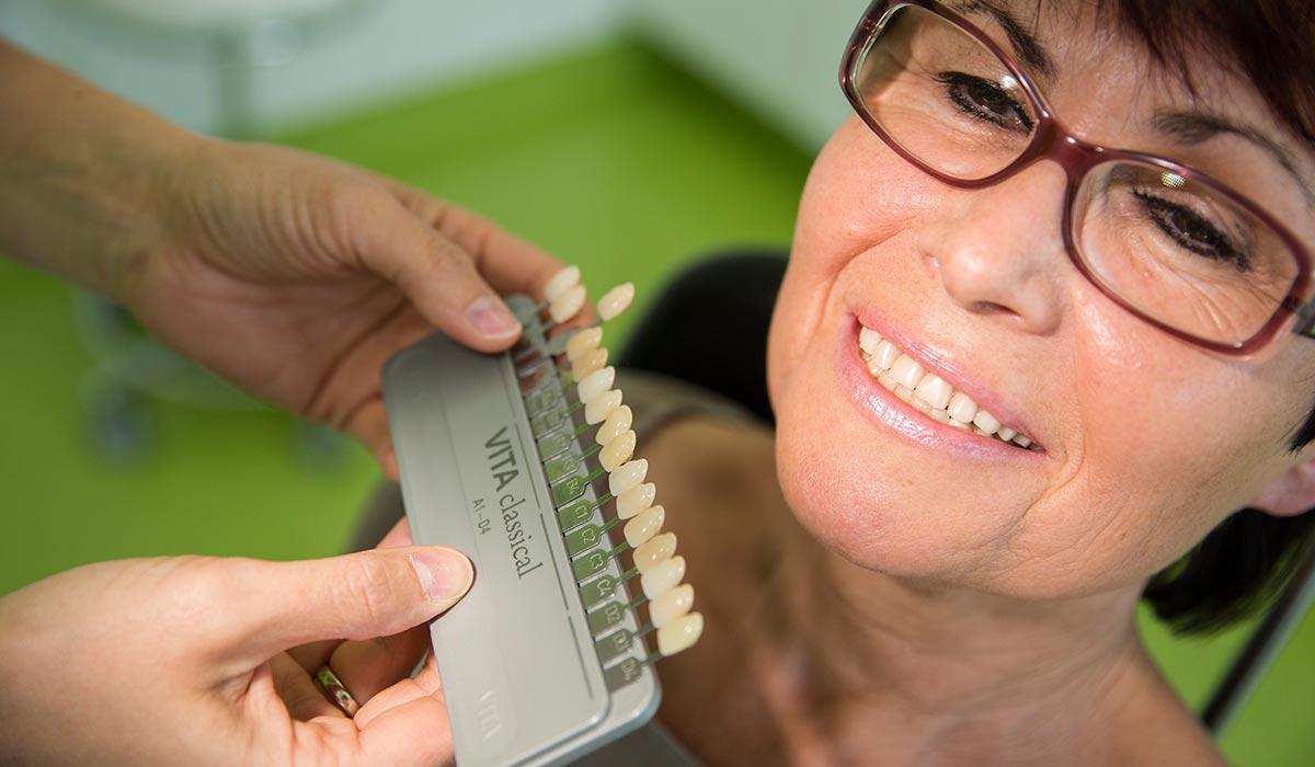 Zwei Frauenhände halten Beispiele für Zahnfarbe an die Zähne einer Frau, die lächelt