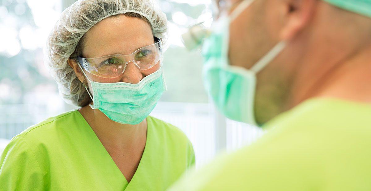 Eine Mitarbeiterin mit Mundschutz schaut Zahnarzt Dr. Thomas Buchmann an, der im Vordergrund zu sehen ist und ebenfalls Mundschutz trägt.