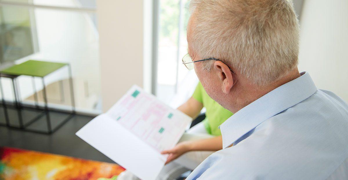 Älterer Patient ist von hinten zu sehen, der im Heil- und Kostenplan etwas nachliest, während eine Mitarbeiterin im Hintergrund den Heil- und Kostenplan hoch hält.