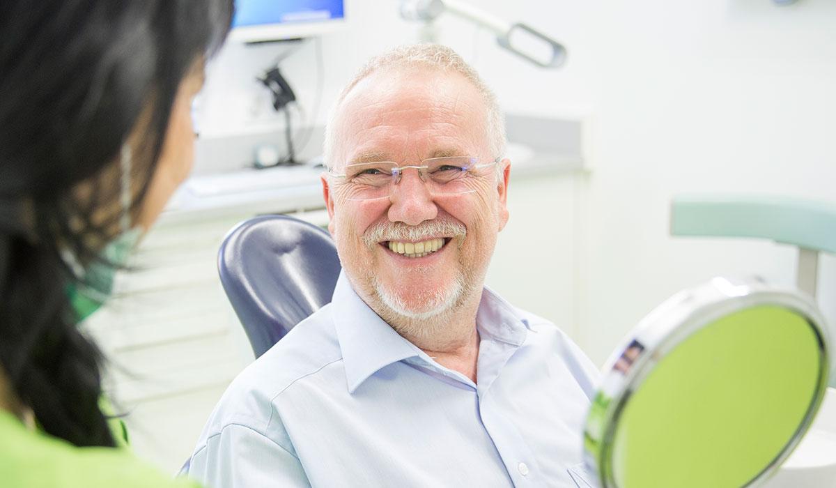 Älterer Patient in einem blauen Hemd lächelt mit neuen festen Zähnen in die Kamera.