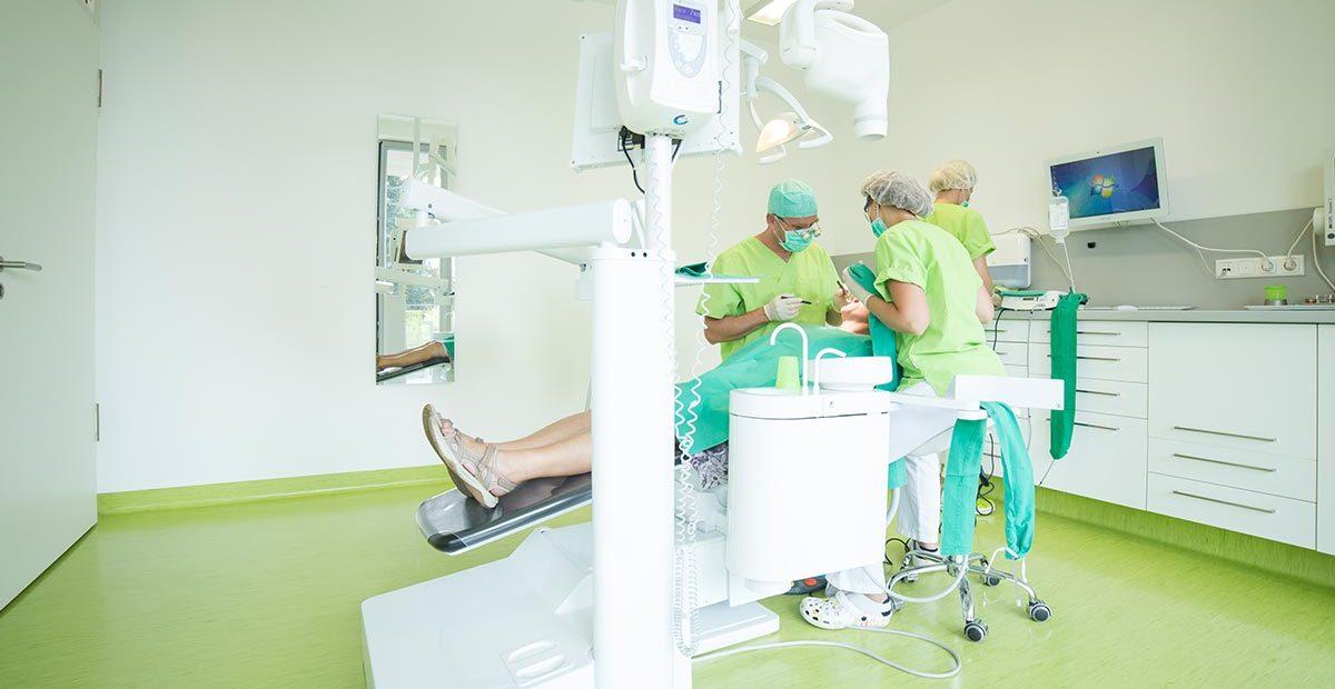 Zahnarzt Dr. Thomas Buchmann und Mitarbeiterin sind vornüber gebeugt und schauen in den Mund eines Patienten, der im Zahnarztstuhl liegt. Im Hintergrund ist eine weitere Mitarbeiterin zu sehen, die Vorbereitungen trifft.