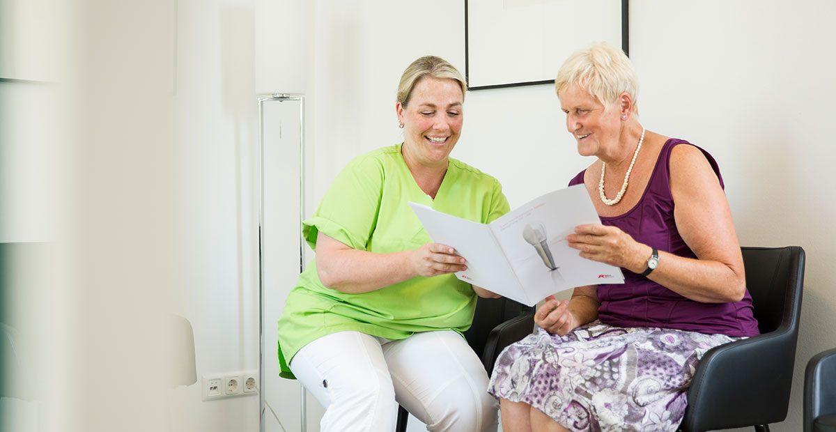 Mitarteiterin Bernadette Mendel sitzt mit einer älteren Patientin im Wartezimmer und erklärt ihr in einem Prospekt etwas zu Zahnimplantaten.