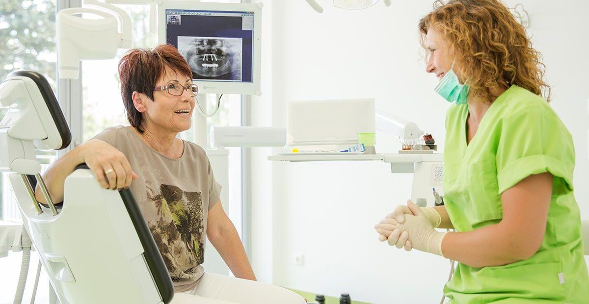 Mitarbeiterin Cornelia Renneberg lächelt Patienten im Behandlungsstuhl an, die zurücklächelt