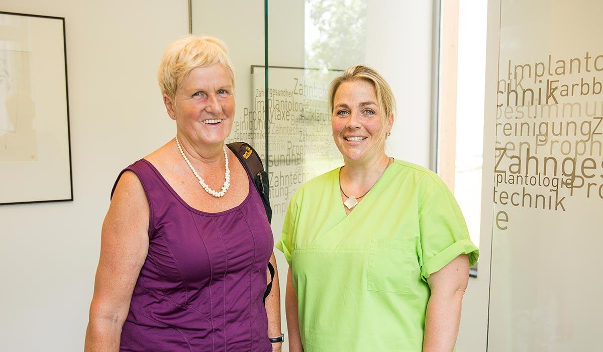 Ältere Patientin steht lächelnd neben Mitarteiterin Bernadette Mendel.