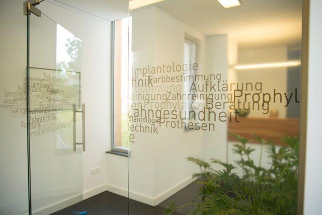 """Die Eingangstür der Praxis Dr. Buchmann mit Beschriftung der Leistungsbereiche """"Implantologie, Farbbestimmung, Aufklärung, Prophylaxe, Beratung, Zahngesundheit, Prothesen"""""""