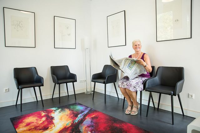 Ältere Patientin sitzt im Wartezimmer und hat eine Zeitung aufgeschlagen, schaut aber lächelnd in eine andere Richtung.