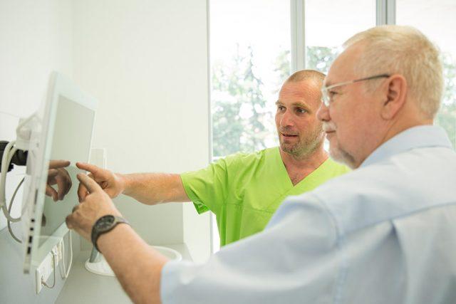 Zahnarzt Dr. Thomas Buchmann und ein älterer Patient zeigen mit dem Finger auf einen Bildschirm.