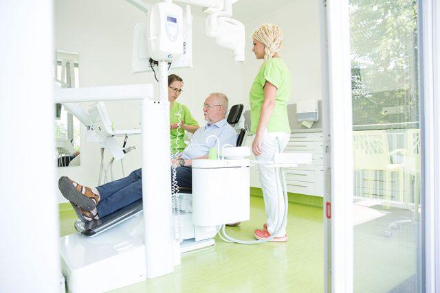 Zahnärztin Karin Kurze sitzt neben älterem Patienten im Stuhl und erklärt ihm etwas, während eine Mitarbeiterin daneben steht.