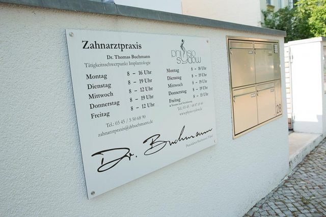 Das Schild der Zahnarztpraxis Dr. Buchmann am Hauseingang mit den Öffnungszeiten der Praxis.