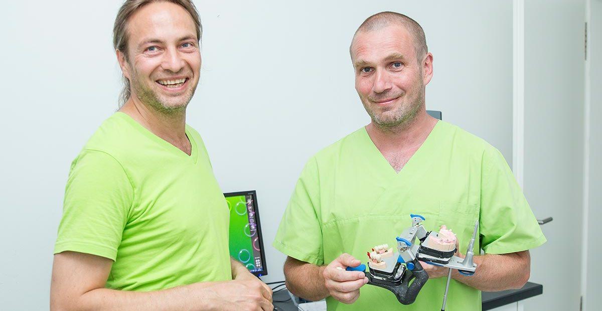 Zahntechniker Thomas Beinroth und Zahnarzt Dr. Dr. Thomas Buchmann, der ein Modell für Zahnersatz in den Händen hält.