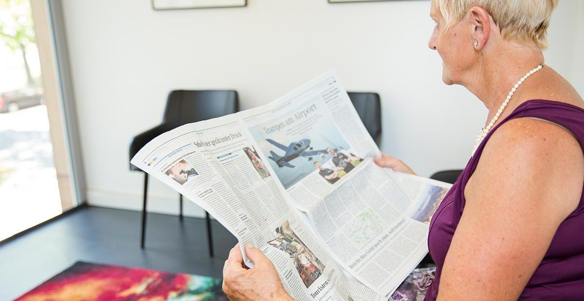 Patientin liest eine Zeitung in der Zahnarztpraxis Buchmann in Halle