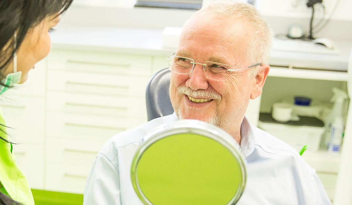 Älterer Patient hält einen Spiegel und lächelt Mitarbeiterin an.