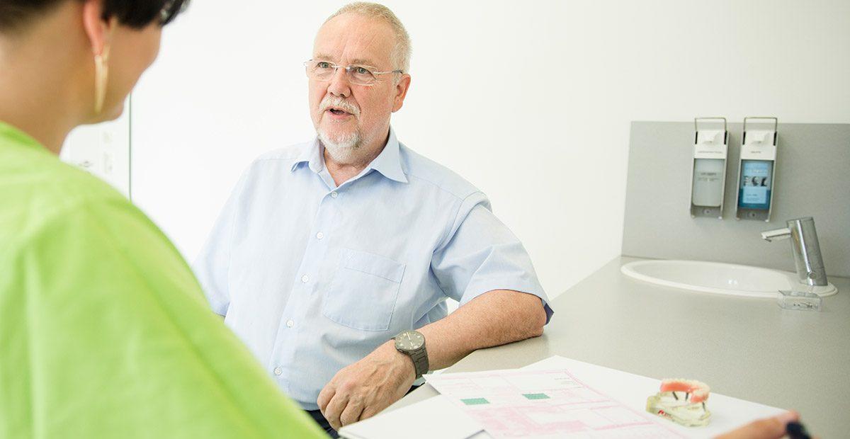 Älterer Patient lehnt mit dem linken Arm auf einem Tisch, auf dem der Heil- und Kostenplan liegt. Im Vordergrund ist eine Mitarbeiterin von hinten zu sehen, die ihn anschaut.