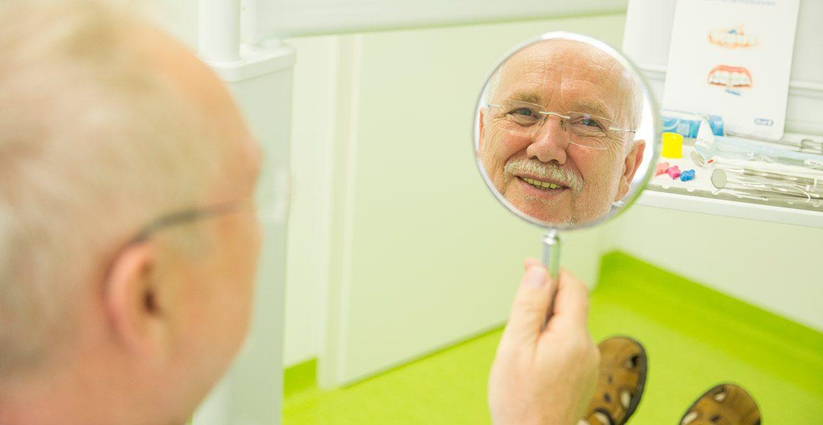 Älterer Patient sieht seine neuen Zähne im Spiegel und lächelt sein Spiegelbild an.