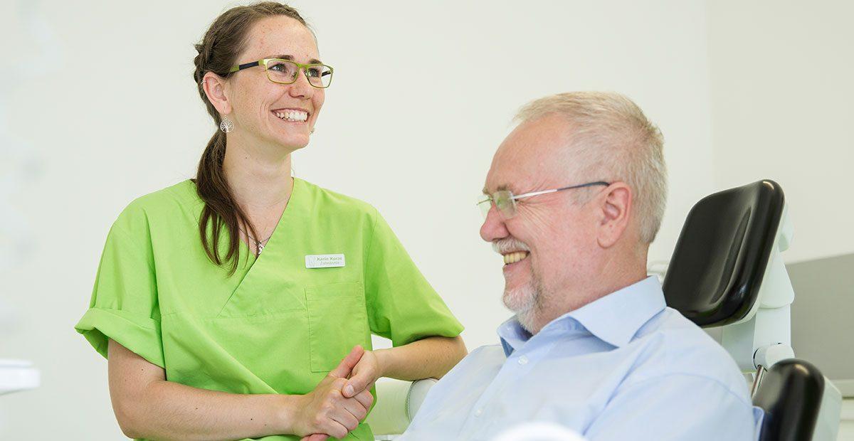 Zahnärztin Karin Kurze steht neben einem älteren Patienten und lächelt.