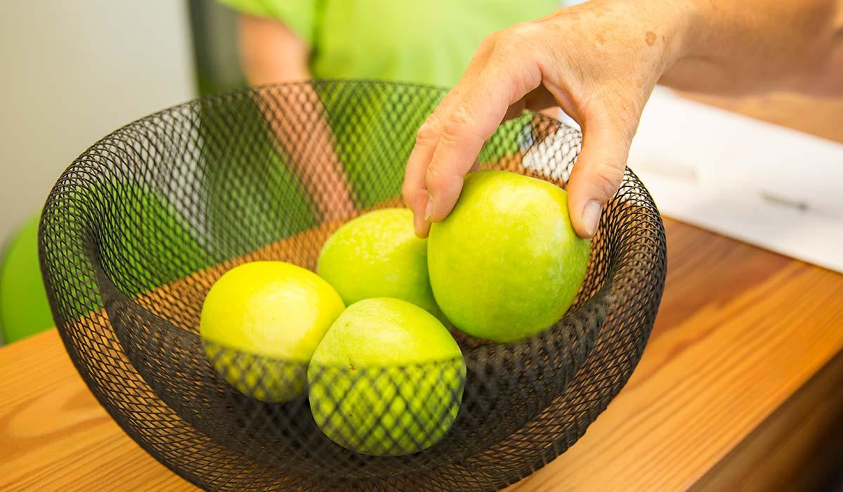 Eine Männerhand greift in einen Korb und nimmt sich einen grünen Apfel heraus.
