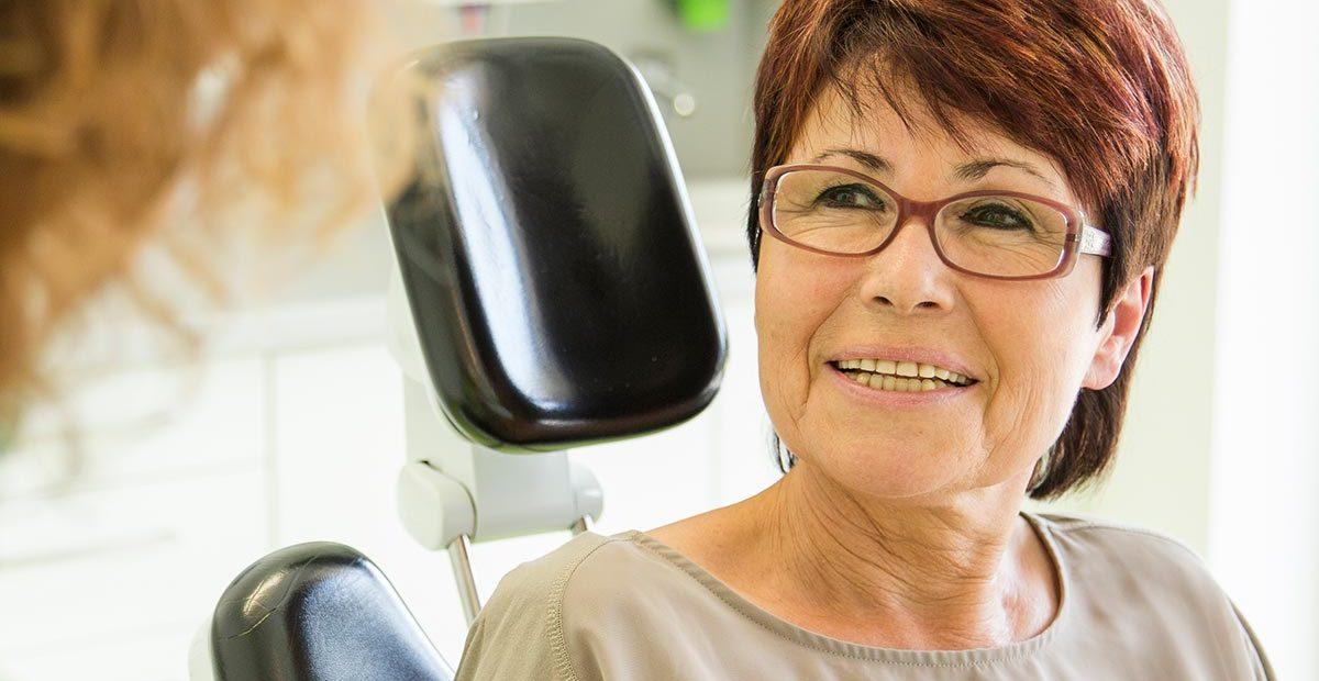 Ältere Patientin lächelt eine Zahnarzthelferin an, von der nur die Haare zu sehen sind.
