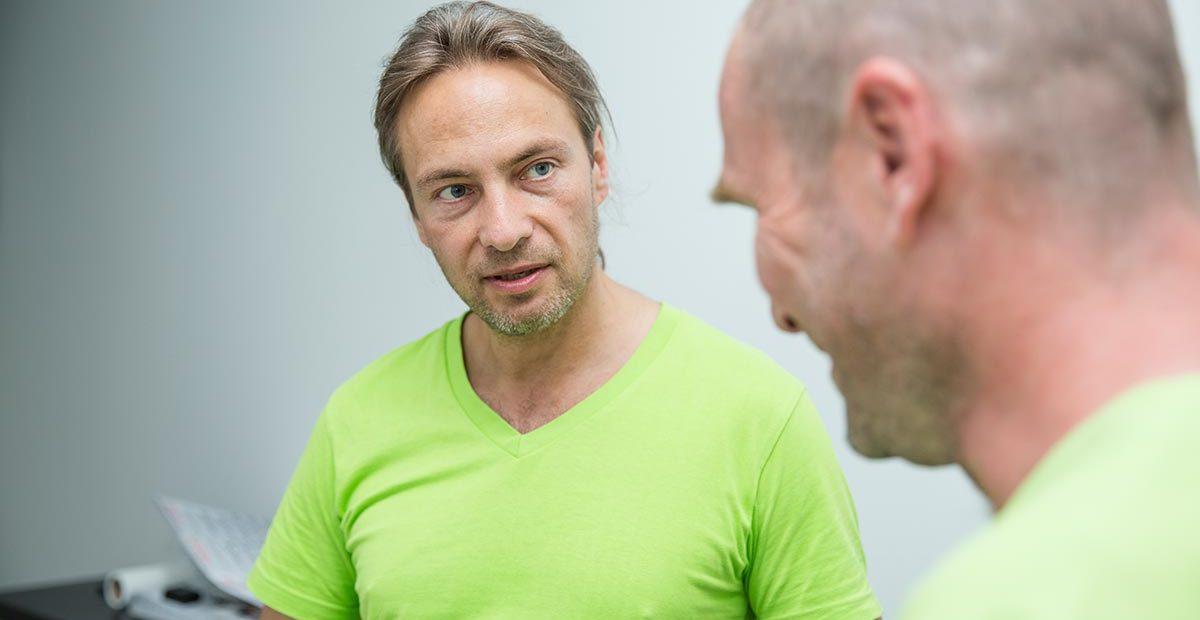 Zahntechniker Thomas Beinroth schaut Zahnarzt Dr. Thomas Buchmann an, der nur von der Seite zu sehen ist, aber lächelt.