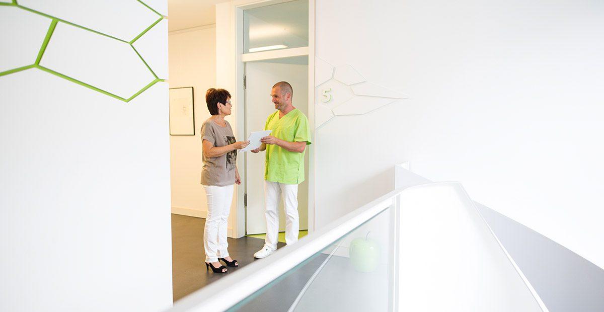 Dr. Thomas Buchmann steht mit einer Patientin vor einer Tür und gibt ihr einen Vorsorgeplan in die Hand. Beide schauen sich an und lächeln.