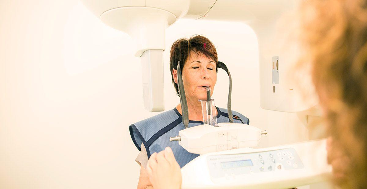 Patientin beißt auf eine Kunststoffvorrichtung in einem 3D-Röntgengerät, das um sie herumfährt. Im Vordergrund ist eine Mitarbeiterin von hinten zu sehen, die das Gerät steuert.