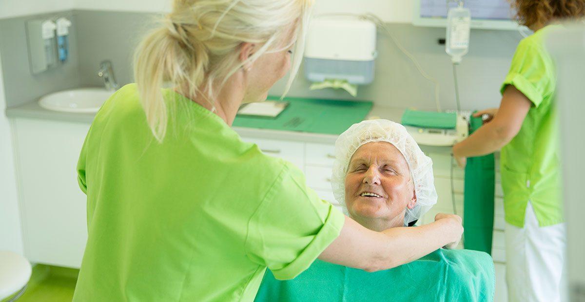 Eine Mitarbeiterin legt einer älteren Frau im Behandlungsstuhl einen OP-Umhang um, während sie angelächelt wird. Im Hintergrund bereitet eine andere Mitarbeiterin einen weiteren OP-Kittel vor.