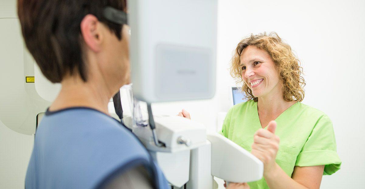 Mitarbeiterin Cornelia Renneberg lächelt Patientin an, die in einem Röntgengerät steht.