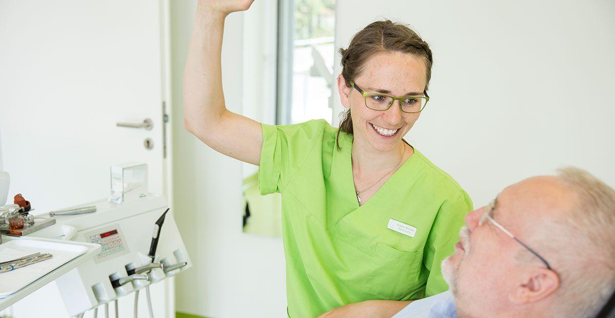 Zahnärztin Karin Kurze lächelt älteren Herrn im Zahnarztstuhl an, während sie das Behandlungslicht mit der rechten Hand ausrichtet. Der Patient liegt im Stuhl und lächelt sie an.