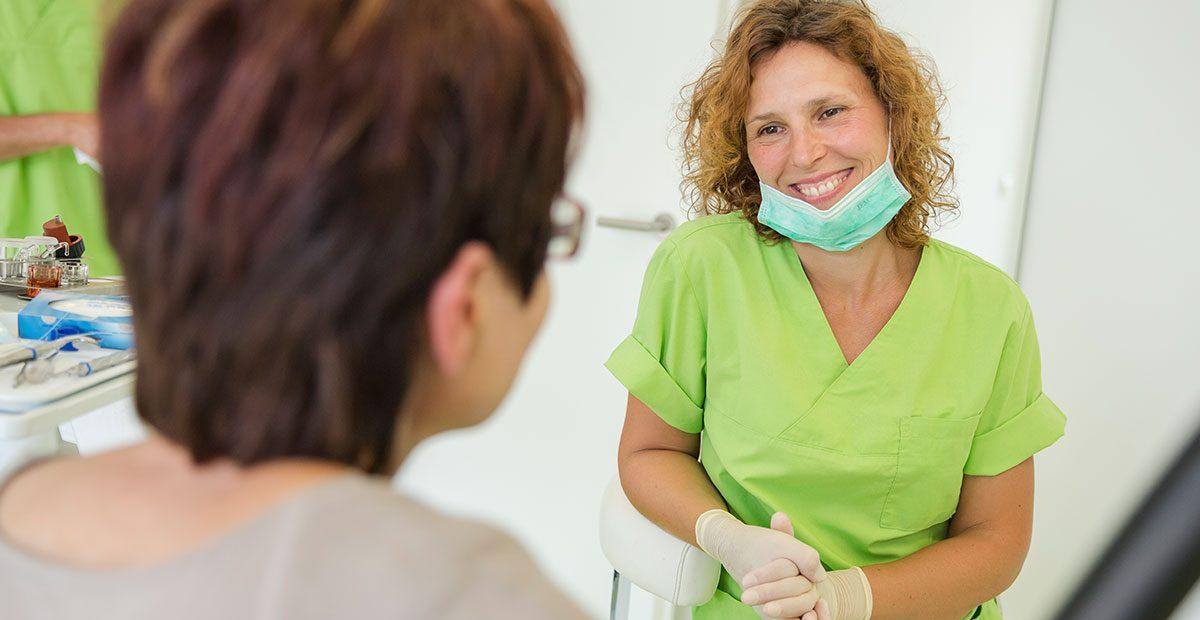 Mitarbeiterin Cornelia Renneberg hat ihren Mundschutz heruntergezogen und lächelt Patientin an.